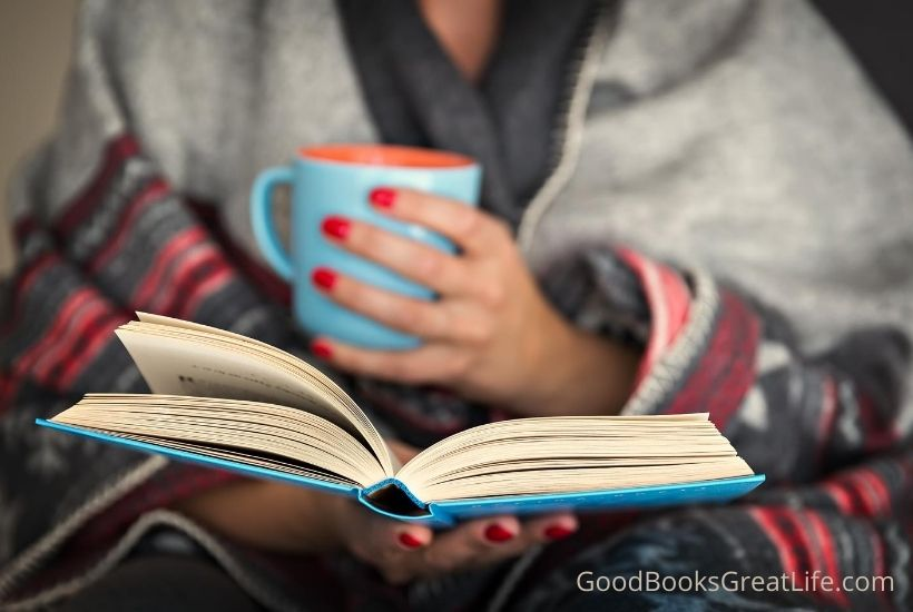 Woman reading book and enjoying a mug of coffee.